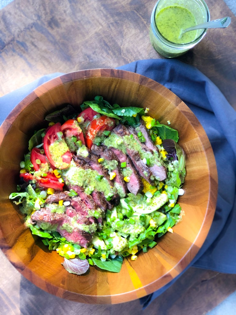 Flat iron steak salad with chimichurri vinaigrette in a wooden bowl from overhead, more vinaigrette in a jar off to the side.