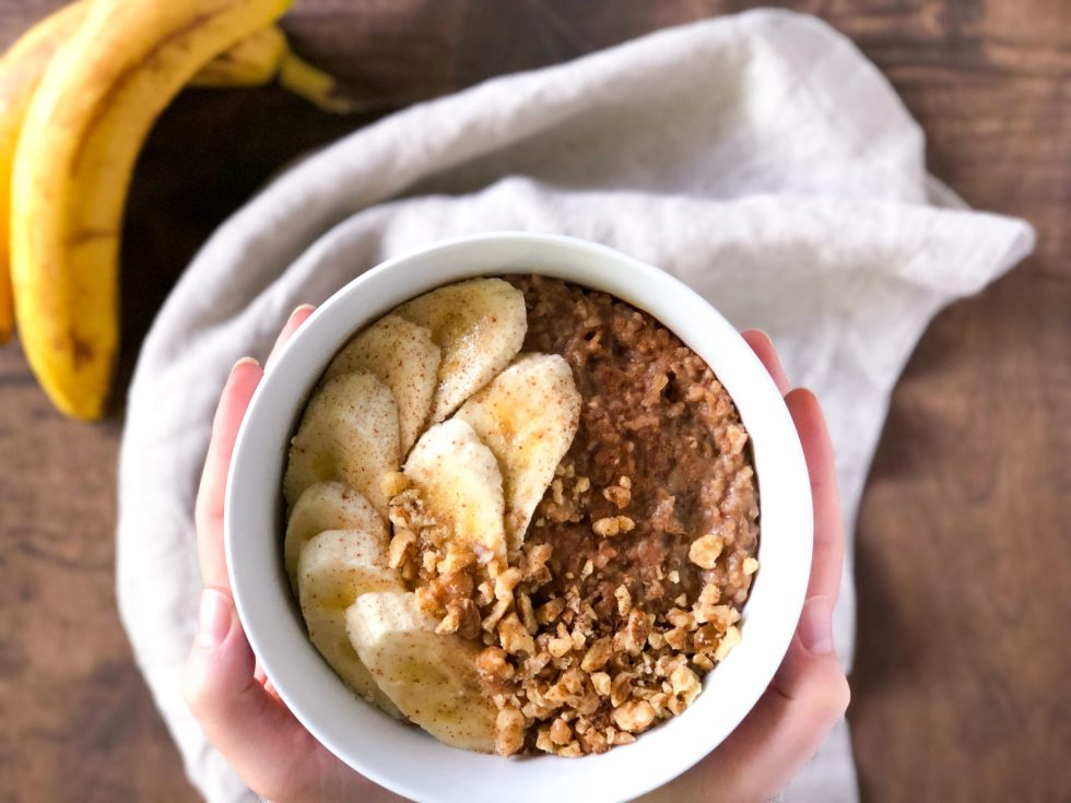 A pair of hands holding a bowl of banana nut steel cut oatmeal over a cloth napkin and overripe bananas.