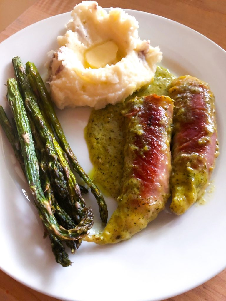 Prosciutto-wrapped Chicken in Pesto Cream Sauce with buttered mashed potatoes and roasted asparagus  on a white plate.
