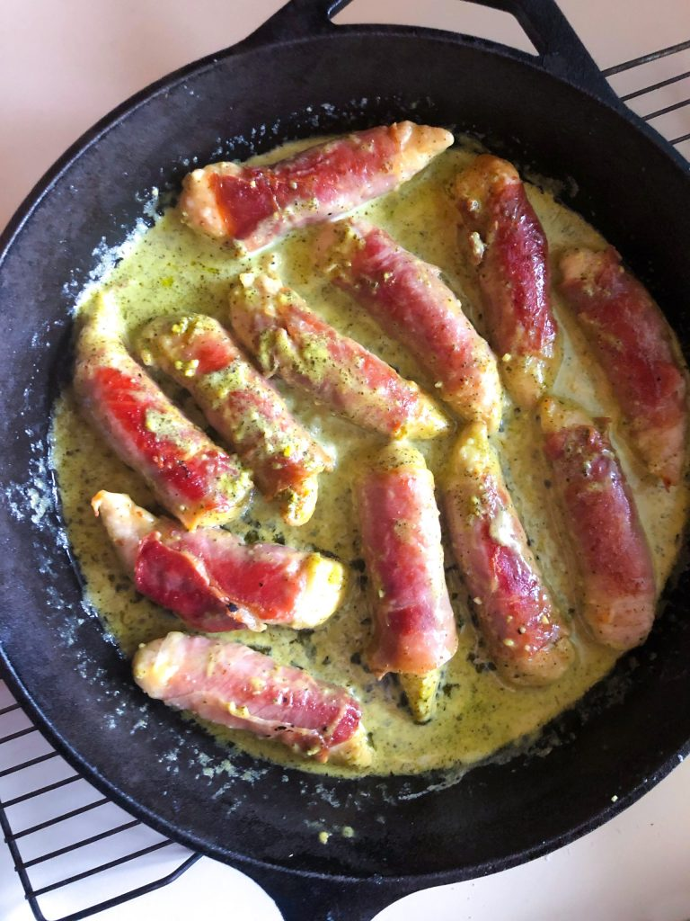 Prosciutto-wrapped Chicken with Pesto Cream Sauce in a cast-iron skillet