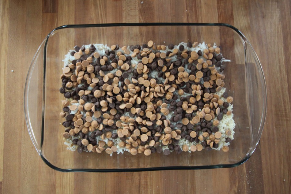 Chocolate chips and butterscotch chips cover the layer of coconut flakes in a 9 by 13 pan. The pan is transparent and sits on a wooden counter.
