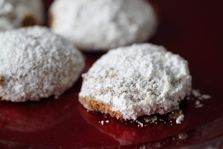 Round cookies doused in powdered sugar sit on a red, reflective plate.