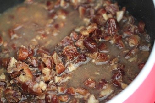 A close-up image of chopped dates mixed with water, sitting in a nonstick pot.