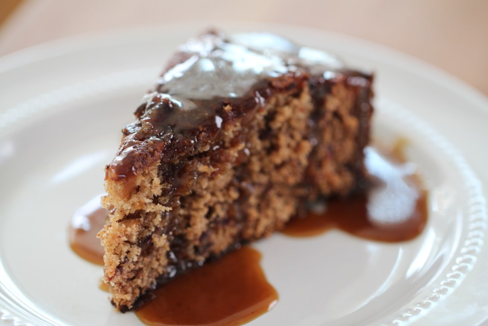 A wedge-shaped slice of sticky toffee pudding dripping with a caramel-colored sauce, all sitting on a white plate.