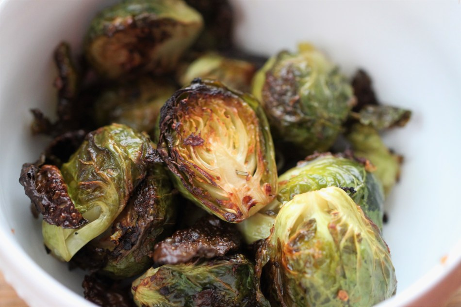 Brussels sprouts with crispy edges sit in a pile inside a white bowl.