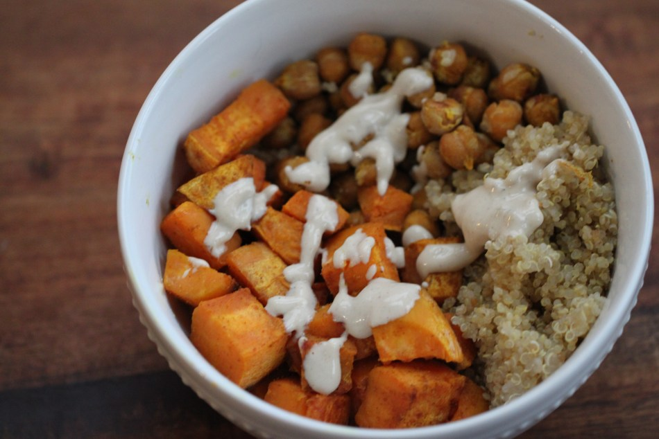 Each component of the meal (roasted sweet potatoes, spiced chickpeas, and quinoa) take up roughly one third of a white bowl, which sits on a wooden surface. The entire meal is drizzled with a creamy white sesame sauce.