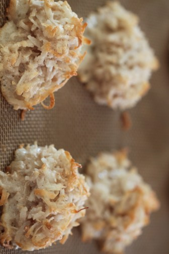 Baked coconut macaroons. The cookies have transformed from stark white haystacks to cream colored, with toasted golden edges.