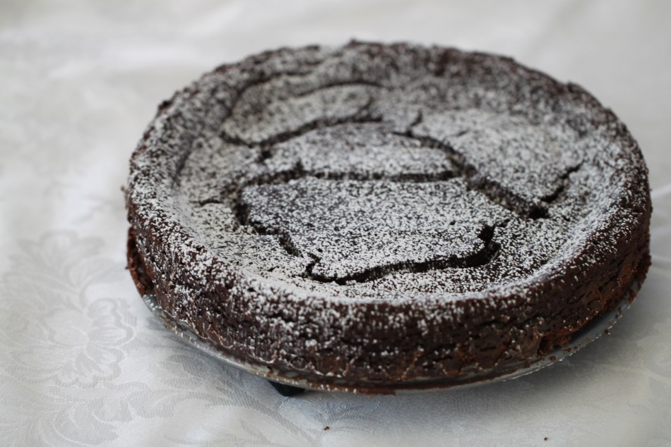 An unsliced chocolate torte sits, dusted with powdered sugar, on a white tablecloth.