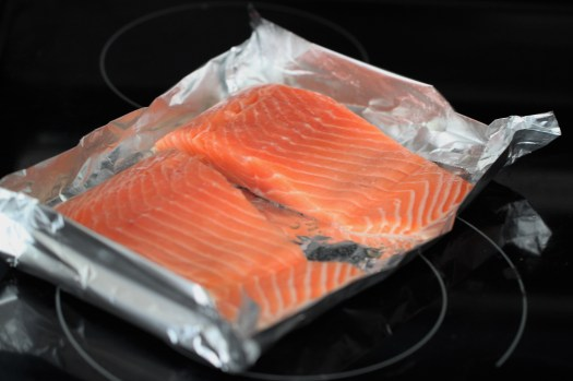 Two pink salmon filets rest side-by-side in a a makeshift aluminum foil tray.