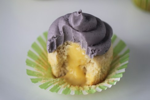 A partially-eaten lemon lavender cupcake sits on a green cupcake wrapper, displaying a cross-section. The cupcake is white, with a purple frosting and a yellow lemon curd filling.