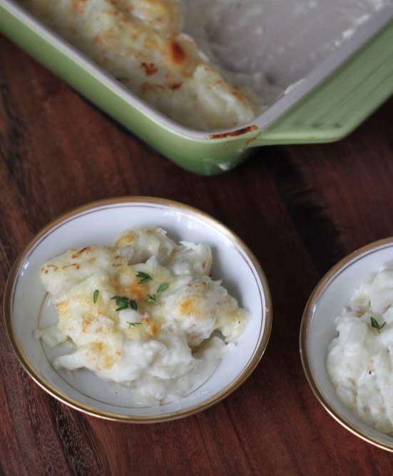 Two bowls of Icelandic fish stew (plokkfiskur) sit in white bowls in the foreground. a small green casserole dish of plokkfiskur rests in the background.