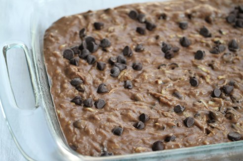 Unbaked zucchini brownies, resting in a greased 9x13 inch pan and laden with an abundance of chocolate chips.