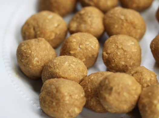 Balls of oatmeal cookie dough sit on a white plate, waiting to be refrigerated.