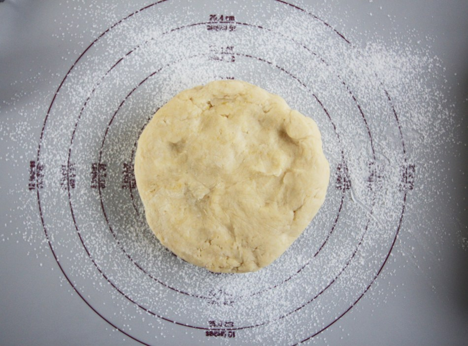 A ball of sweet shortcrust pastry sits on a silicone mat that has been covered in flour. It is ready to be rolled out and placed in a pan.