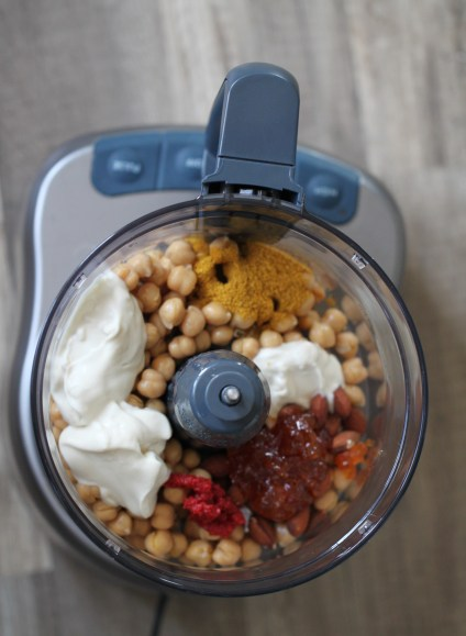 The base ingredients for this vegan coronation salad - chickpeas, vegan mayonnaise, apricot preserves, tomato paste, curry, and turmeric - rest in a food processor, ready to be mashed together.