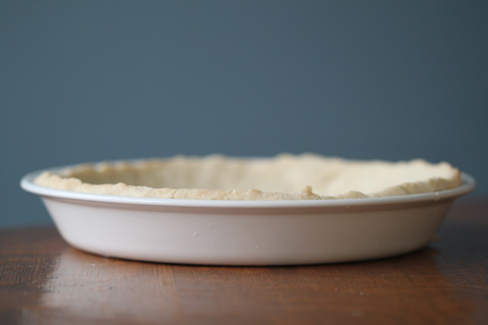 An empty, baked pie crust sits in a white pie pan on a wooden surface, against a blue backdrop. This pie crust was made using gluten free flour; it can also be made vegan.