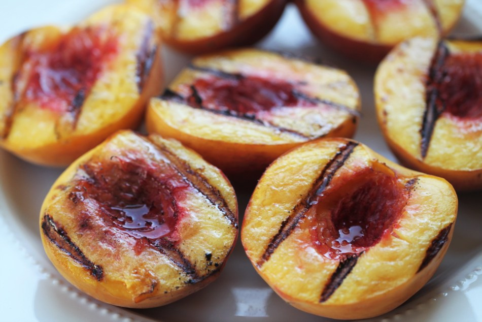7 peach halves sit on a white plate. They have been brushed with butter and grilled; their surfaces feature dark black char marks from the grill, as well as a small amount of brown caramelization.