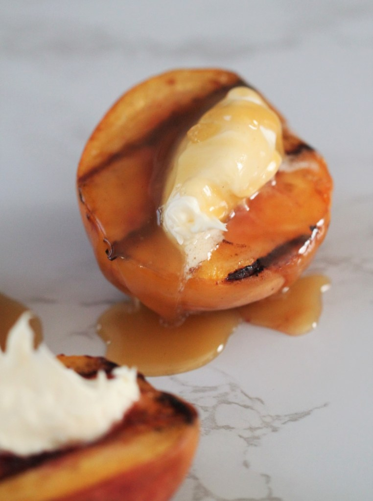 A bright orange peach sits on a white marble countertop. It is topped with white whipped vanilla mascarpone cheese. A golden bourbon caramel sauce is dripping over the mascarpone onto the peach. A few drips are spilling onto the counter.
