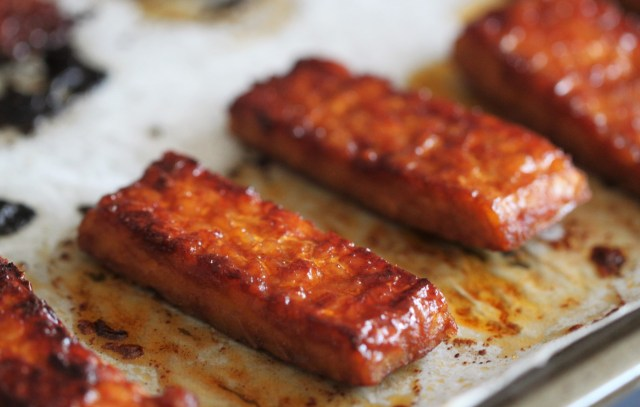 Strips of reddish orange vegan tempeh bacon rest on a sheet of parchment paper.