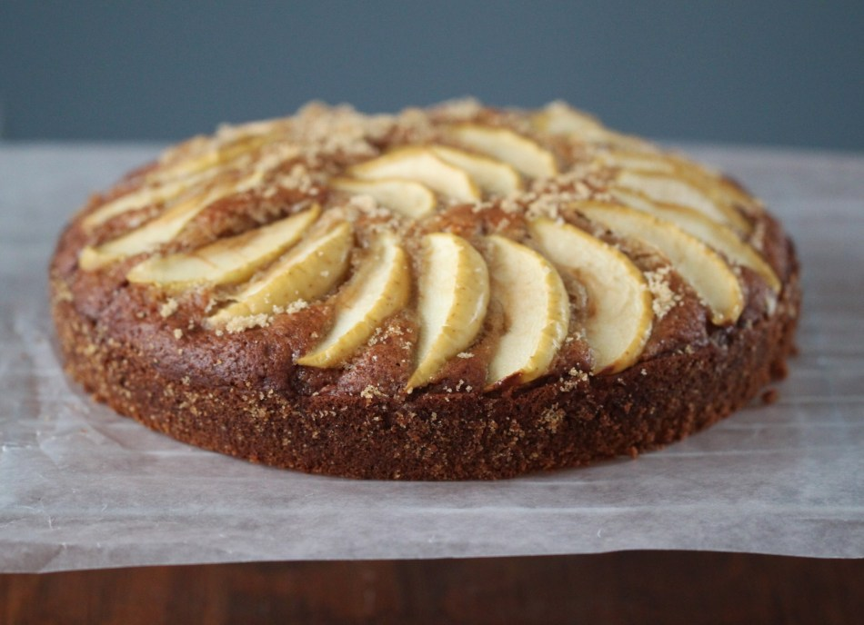 A spiced apple cake rests on a cooling rack, atop a piece of wax paper. The cake is topped with slices of an apple and has been dusted with brown sugar.