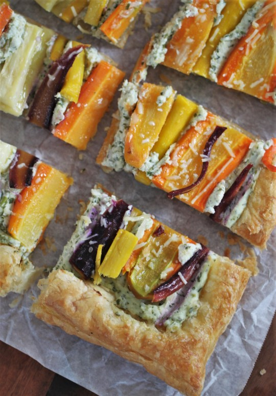 A savory carrot ricotta tart is cut into rectangular slices and sits on a piece of parchment paper, which rests on a wooden surface.