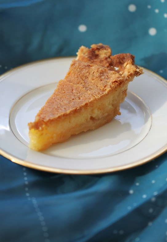 A custardy slice of chess pie sits on a white plate against a blue, starry background.