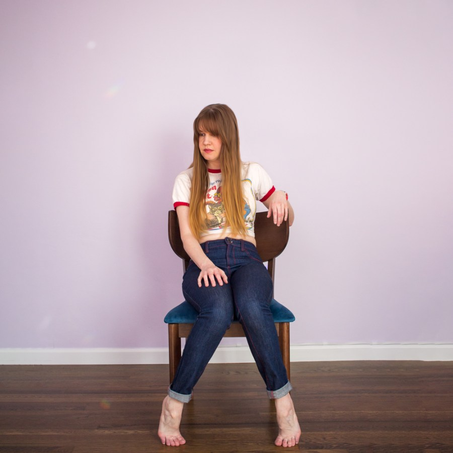 girl in handmade denim jeans with red topstitching sitting in a chair against a lilac wall