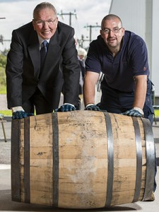Former Benromach stillman Tom Anderson (L) and Brian Williams roll the first cask of whisky into Benromach's new warehouse August 8, 2014. Image courtesy Gordon & MacPhail.