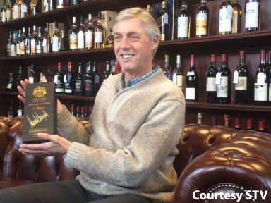 "Colin Plint with the signed bottle of ""Trump Scotland"" whisky at McTear's January 13, 2017. Image courtesy STV."
