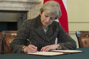 British Prime Minister Theresa May signs the letter invoking Article 50 of the Lisbon Treaty. Image courtesy HM Government Press Office.
