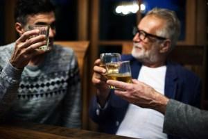 Padre e hijo brindando con whisky el Día del Padre