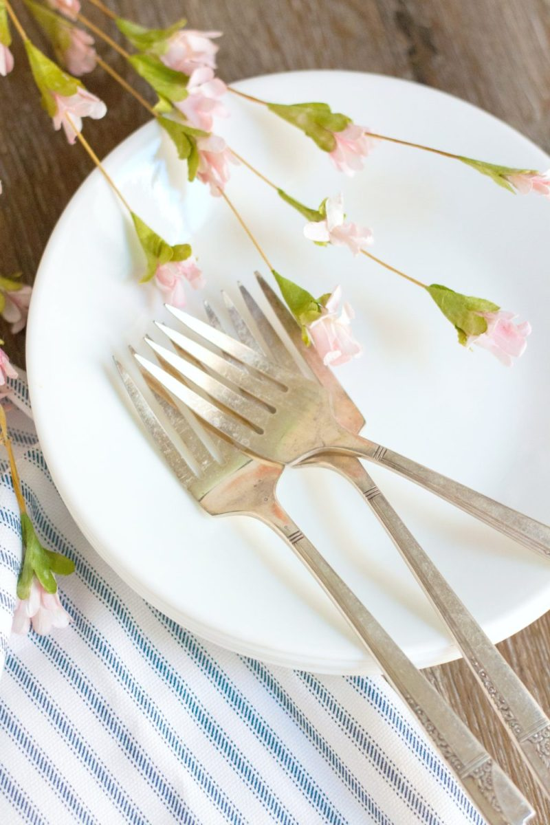 A plate is adorned with vintage forks and small pink flowers.