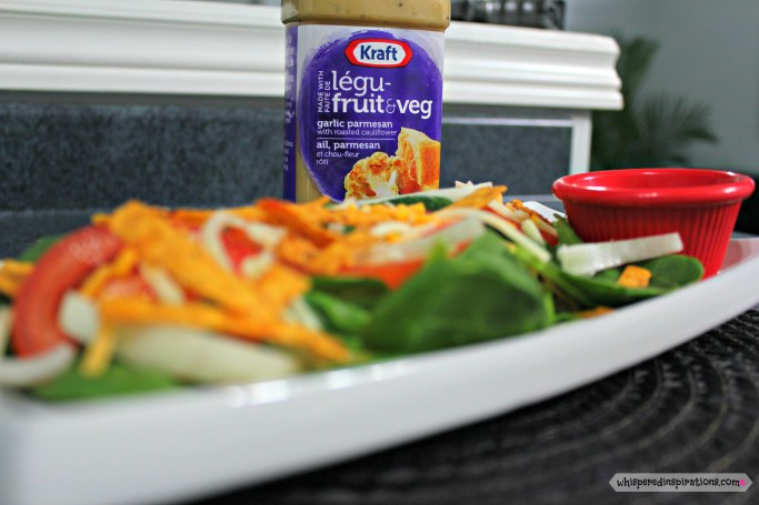 Skinny Spinach Salad is shown on a long plate with NEW Kraft Pourables dressing is in the background.