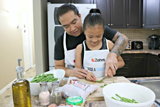 A little girl and her dad chop vegetables together.