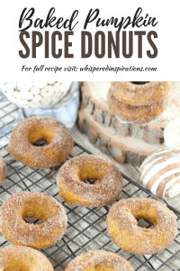 Baked pumpkin spice donuts on a cooing rack, woody and rustic decor surround them. They look delicious with sugar and cinnamon.