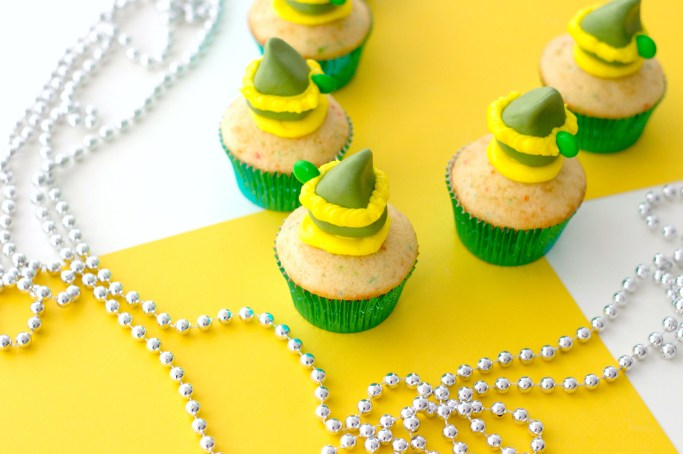 Final product with 5 Buddy the Elf cupcakes shown against a yellow and white background and silver bead garland.