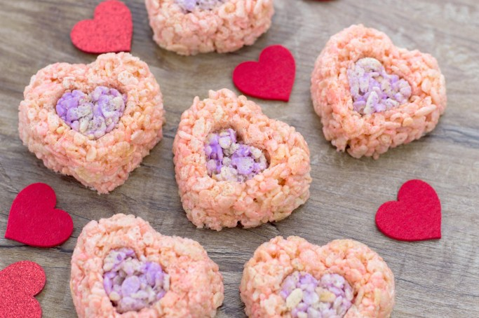 The finished Valentine's Day Rice Krispies Treats on a wooden board with felt hearts as decoration.