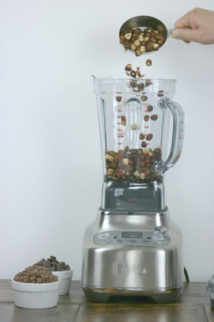 Roasted hazelnuts being poured into blender.