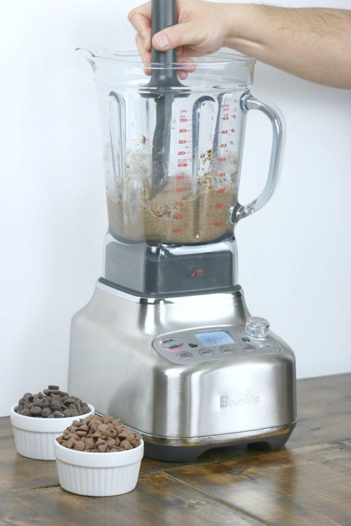 Scraper being used on nuts inside blender.