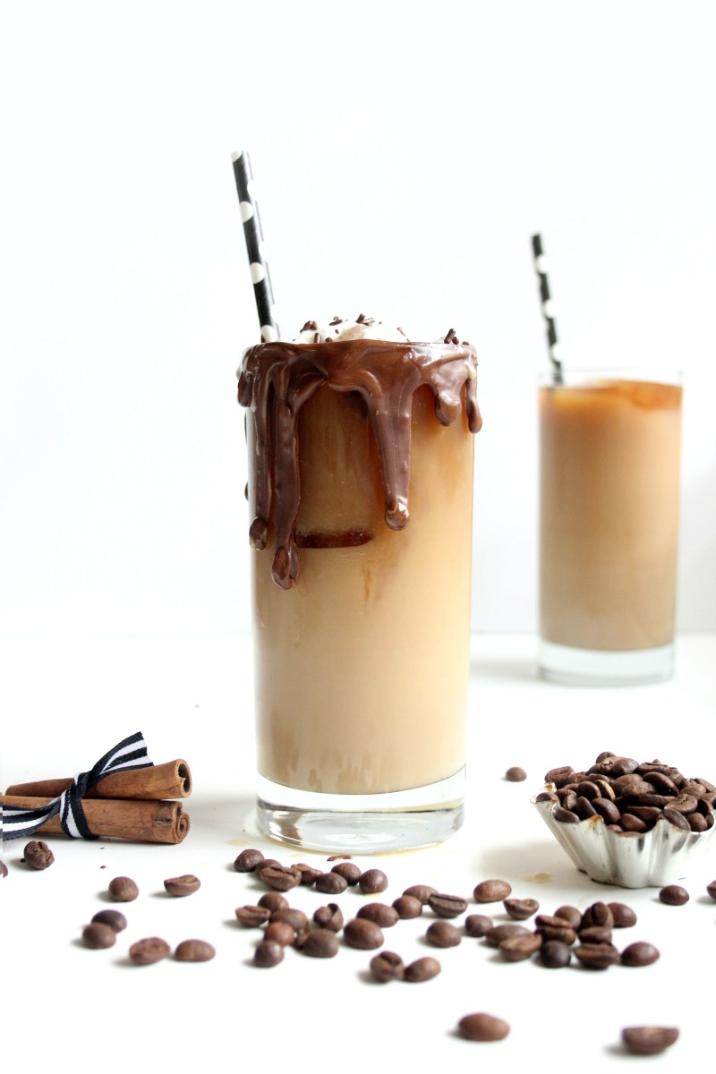 Glass of vanilla iced coffee with chocolate dripping.