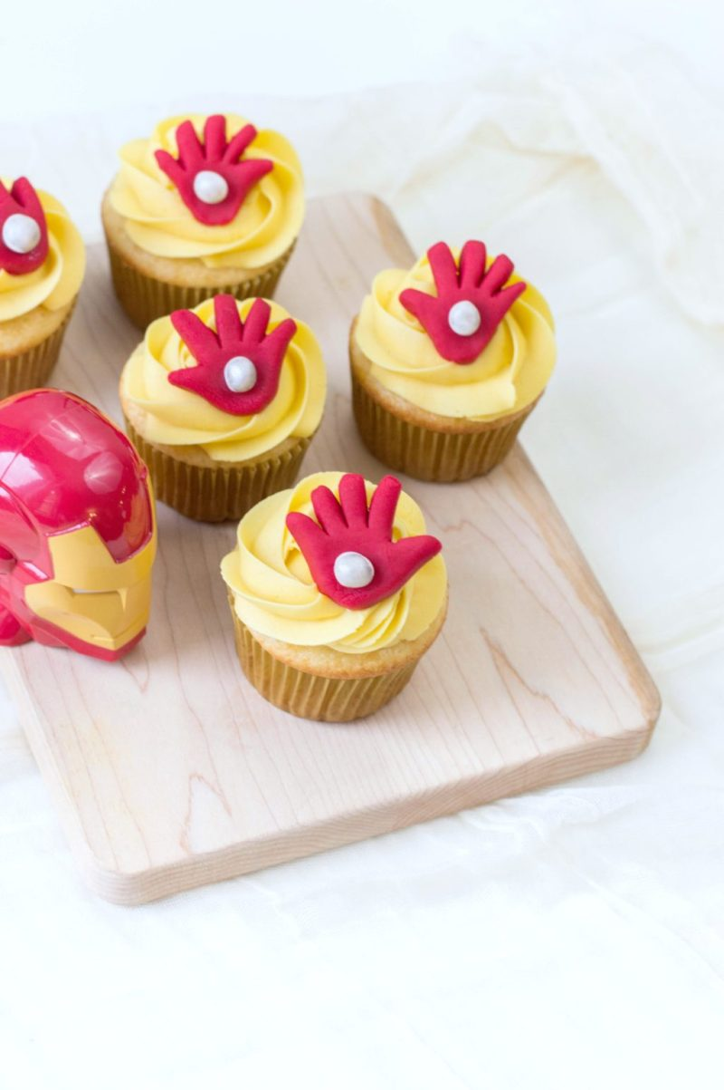 Top view of 5 cupcakes on a wooden board with Iron Man mask as decor.