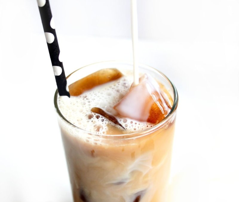 Milk is being poured on coffee ice cubes and iced coffee mix.