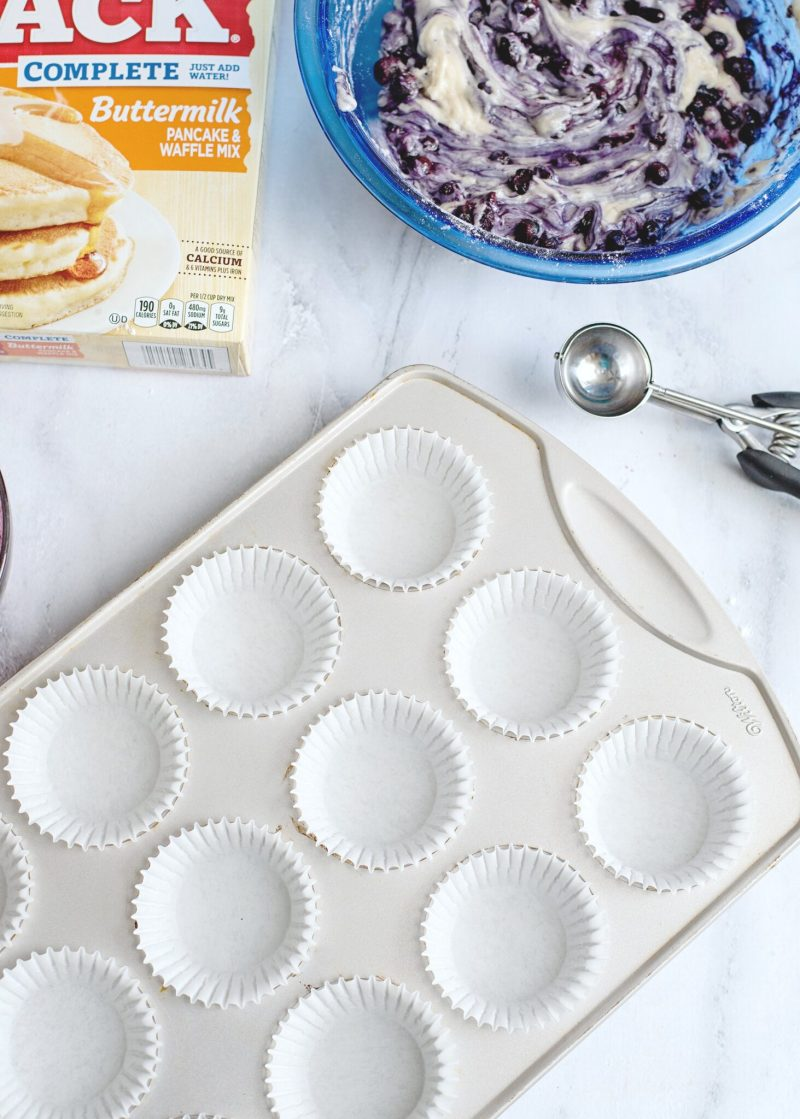 White muffin liners are placed in a muffin pan. The batter, ice cream scooper and batter are also pictured.