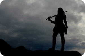 The silhouette of a warrior woman with storm clouds in the background.