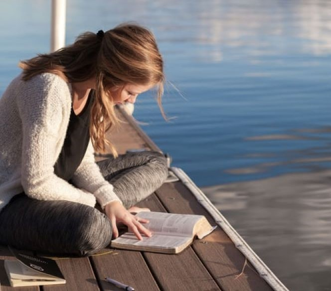 woman reading bible by water empower the mind whispers of worth