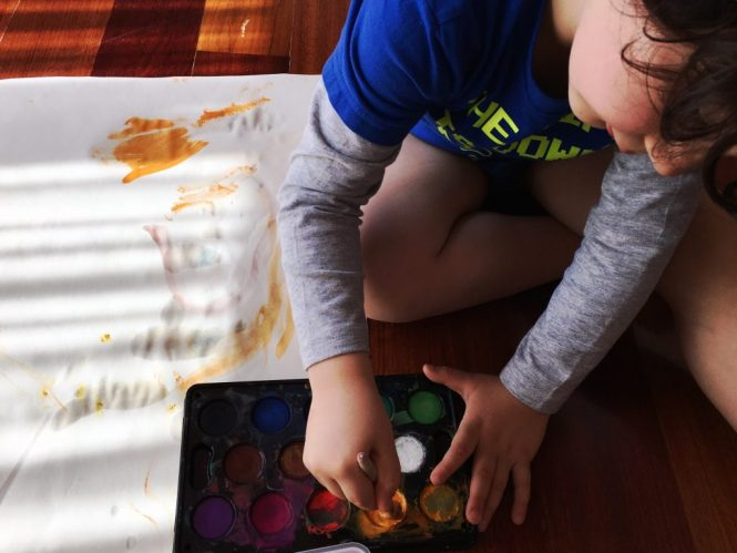 Boy using watercolour to finger paint
