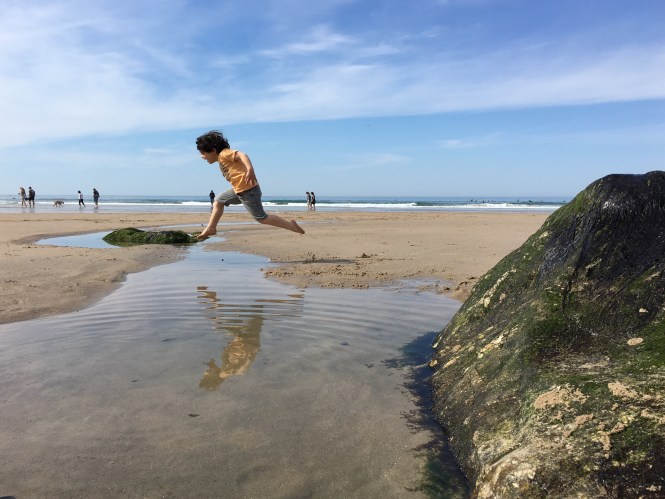 Child doing a Big jump over rock pool action shot
