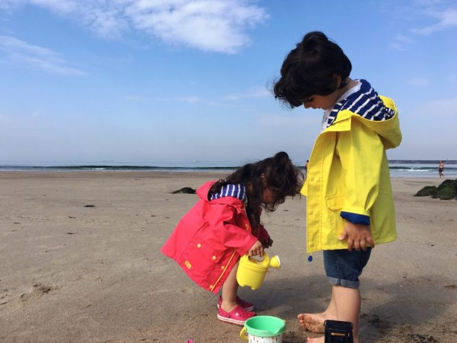 Brother and sister playing at the beach - lighthouse ss17 coats