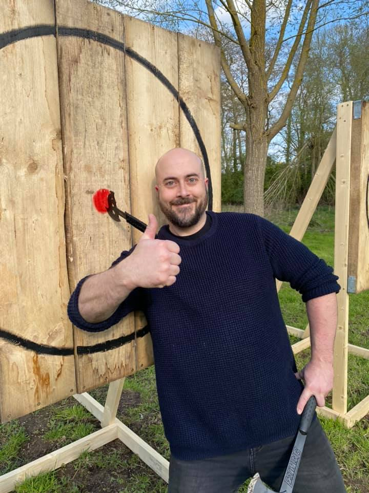 Happy man with an axe he has thrown into the bullseye of a target