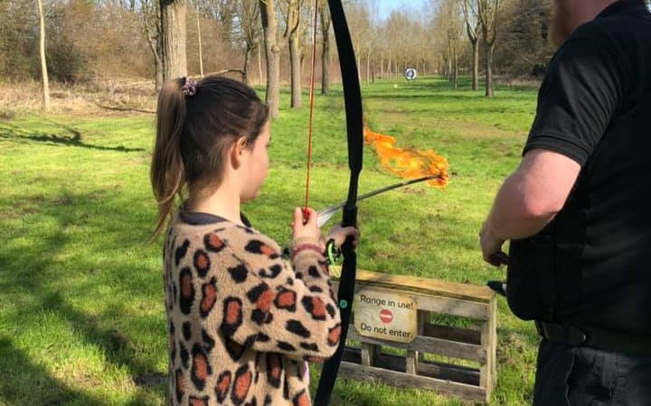 Young girl being coached in shooting a flaming arrow.